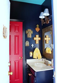 Bold black bathroom walls with red door - love the collection of 21 crosses eclecticallyvintage.com