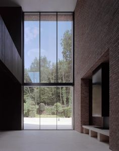 A grand window faces into woodland in a north London house by Carmody Groarke.
