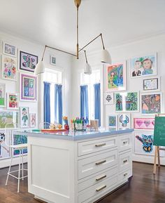 The most fun playroom designed by @collins__interiors 📷@nathanschroderphoto.  Adore the framed children's art!! Happy Friday!! • • • • #art #playroom #kids #kidsroom #craftroom #island #organization #circalighting #stool #designchic #artistsoninsta