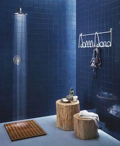 carrelage salle de bain bleu marine avec douche encastrée et tabourets en troncs