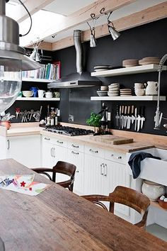"Lately, I've been having a crush on one-black-wall kitchens. I just find them so inspiring and stylish, especially if you have green plants to contrast with.  Warning: the black on the one wall will tighten up the place a bit, so you want light colored furniture and plates.   Tip: if you think about remodelling your kitchen like this, perhaps you'd also like the ""blackboard"" kind of wallpaper, the one where you can draw things on :)   Click here: http://www.foodyhomes.com/po"
