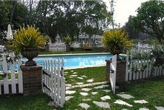 I love the brick, love the picket fence. I would do this around my pool in a heartbeat. I'm a sucker for brick and picket fences. found this on full bloom cottage blog.