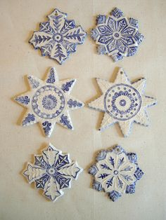 Christmas star snowflake ceramic decorations. Impressed with a lino cut block and decorated with white slip with blue cobalt oxide decoration painted over the texture and a transparent glaze on the top.