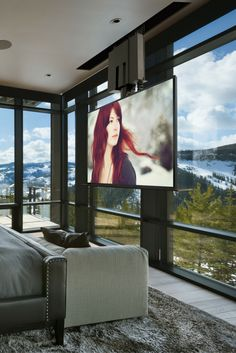"""Amazing view of the mountains in this luxurious bedroom with floor-to-ceiling windows. The drop-down 75"""" TV lets you keep the view while still having a TV in your room."""