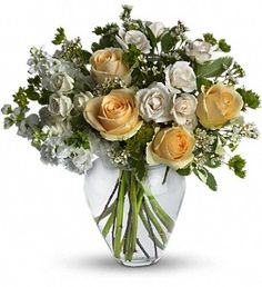 Fresh flowers such as peach roses, crème spray roses, white stock, waxflower and more are gathered in a beautiful clear vase.