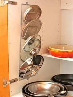 Magazine Rack for Pot Lids  Getting all those pot lids in line is a snap with this organization idea from Aimee Wimbush-Bourque. Just screw a metal magazine rack into the back of a cabinet door and arrange lids by size. The sleek design not only makes it easy to find the right lid but also opens up some additional cabinet space, too