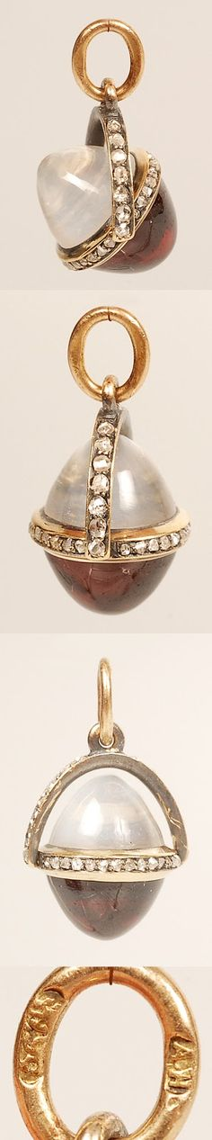 Faberge's pendant. This one was made by Fabergé's workmaster August Hollming, around 1890. The egg is put together by a cabochon moonstone, and a cabochon garnet, held together by a gold band set with rose-cut diamonds. On this band a diamond-set arch is attached, which makes it possible for the egg to swivel and rotate around it's own axis. The hight of the pendant is 3/4'' (1.9 cm)