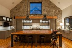 Kitchen features a large wooden island, a stone wall and vaulted ceiling in this home by Surround Architecture × Modern Rustic Homes, Modern Tiny House, Modern Farmhouse Exterior, Barn House Design, Dream Home Design, Modern House Design, Mountain Home Exterior, Mountain House Plans, Wooden Island