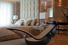 Quarto em tons claros com uma peça lindíssima, a chaise do inesquecível Oscar Niemeyer.