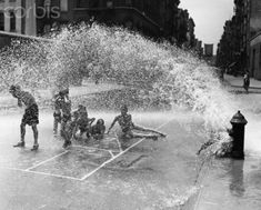 Yes, it's that most familiar of summer scenes on our urban streets- urchins cavort as the fire hydrant sprays cool water. — Image by © Underwood & Underwood/CORBIS