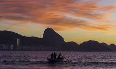 Homens navegam no mar de Copacabana Thiago Lontra / Agência O Globo