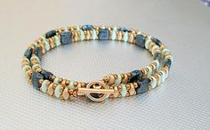 A beautifu bead wrap bracelet of jet picasso tila and gold and pale green super duo beads. This is a unique and trendy bracelet. It will go with a nice