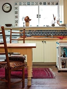 Mexican tiles take this Northern California kitchen to a different place and time. Other collected objects, like blue glass knobs, chair cushions, and an Oriental rug, make this space feel comfortable and cozy. (Photo: Thomas J. Eclectic Kitchen, Boho Kitchen, Eat In Kitchen, Kitchen Decor, Fiesta Kitchen, Global Decor, California Style, Northern California, Kitchen Window Treatments