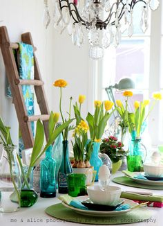 Yellow daffodils & tulips in vintage blue bottles. Lovely
