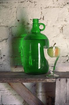 Big Green Bottle - Country still life photography with simple composition of big green bottle and glass of water with reflections on white brick wall in rustic summer house in sunny day light  by Nikolay Panov - http://pixels.com/featured/big-green-bottle-nikolay-panov.html