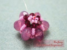 Tutorial : Flower Motif #5 Level : Beginner Equipment : - 4mm Swarovski Bicone - 9x6mm Czech Firepolished Glass Donut Rondelle - 11/0 Seed Bead - Clear Nylon Thread No.25 You can use smaller or bigger rondelle beads. 1. Cut one thread around 60 cm. and make a ring of six seed beads. 2. Add one…