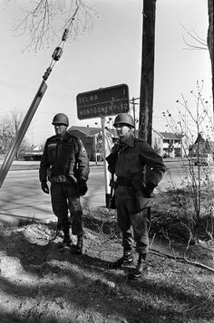 In this March 20, 1965 file photo, National Guardsmen, called to active federal duty by President Lyndon B. Johnson to protect marchers planning to march from Selma, Ala. to the state capitol at Montgomery, stand under a road sign showing the distance to the capital. The demonstration ended at the capitol building in a rally protesting voting regulations in Alabama.