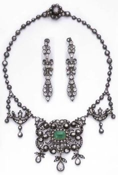 Antique parure, circa 1840. Consisting of a necklace and a pair of ear pendants. The necklace set throughout with rose-cut diamonds, the central element set with an emerald cabochon within a foliate motif, suspending three rose-cut diamond drops, the pair of earrings set with paste, mounted in gold. #antique #necklace #earrings