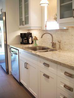 White Shaker style cabinets with modern brushed nickel hardware. Kashmir White Granite Countertops and Venus Marble Mosaic in Milky Way backsplash