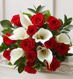 love it! red roses with bright white calla lillies and some green for definition. Perfect fro a christmas wedding!