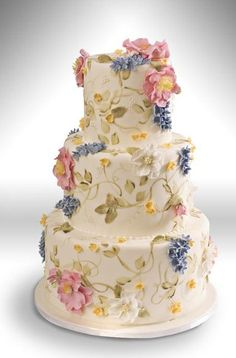 Painted leaves and vines accent this three tier wedding cake adorned with blue and pink sugar paste flowers