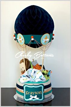 This hot air balloon diaper cake is ready for its journey home to a new little boy and his family. My most difficult creation yet, this gift defied every creative instinct I have, but I'm proud to show it off to you all here. This gift is created with: 18 Pampers Swaddlers (size 1), 2 baby body suits, 2 baby washcloths, 1 boys' jumper suit, 1 pair baby booties and 1 monkey soft toy.
