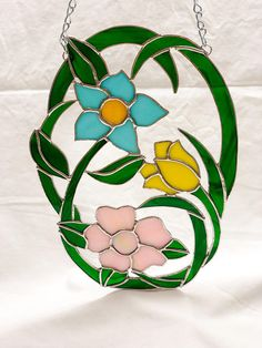Enjoy this beautiful three flower stained glass suncatcher! This wonderful piece has three flowers with winding stems and leaves. The three flowers are gorgous premium pastel colored glass with green swirl for the stems and leaves. Is spring your favorite time of the year and do