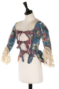 Caraco bodice, France, ca. 1780, fabric: early 1760s. Blue silk brocade, woven with lacy ribbons trails, plumes and bouquets, lined in glazed pink cotton, tartan ribbon ties to fasten.