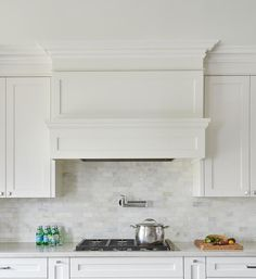 A nickel swing arm pot filler is mounted to white and gray mosaic marble backspl. - A nickel swing arm pot filler is mounted to white and gray mosaic marble backsplash tiles between a - Stove Vent Hood, Kitchen Vent Hood, Oven Hood, Kitchen Stove, Kitchen Backsplash, Kitchen Redo, Kitchen Design, Kitchen Range Hoods, Stove Hoods