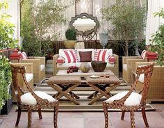 This outdoor patio truly feels like a room, thanks to curtains of Sunbrella fabric in natural with red trim from West Coast Trim. Indian inlaid Regency-style chairs are from Singh Imports. The striped outdoor rug is from Ceylon et Cie; the pair of rattan ottomans and the wooden sphere on the coffee table are from Mecox Gardens; the resin wicker sofa and chairs are from Restoration Hardware. A Moorish-inspired mirror hangs from the pergola on industrial chains. On a table under the mirror are…