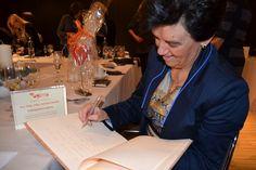 Pilar Gómez Acebo realizando una dedicatoria en el libro de visitas de Agima después de recibir la placa como Embajadora de las Agimas