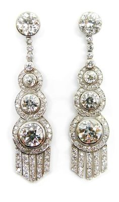Pair of graduated brilliant cut diamond cluster pendant earrings, French, the three tiered diamonds in overlapped articulated diamond borders, suspending diamond set fringes, from collet diamond tops with a line of smaller stones in between, open collet set in platinum, stamped serial number 022398
