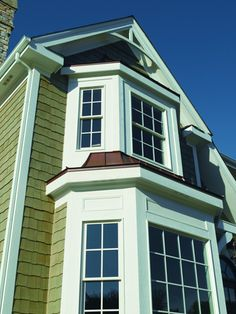 The green of this house pairs wonderfully with the white Andersen 400 Series Tilt Wash Double Hung Windows.