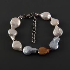 Náramek barevné perly LI451. Jedinečný náramek s barevnými perlami. Náramek je vyroben ze šlechtěných sladkovodních perel o velikosti cca 15x10 mm; perly jsou mezi sebou navázany uzlíkovou metodou. Délka náramku je 18 - 22 cm. Barva perel je bílá, modrá a bronzová s přirozenými odlesky. Orientační váha 11,2 g. Náramek byl vyrobena v České republice.
