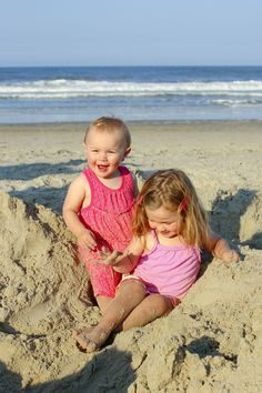 Two tiny sisters playing in the sand at the beach. By Calm Cradle Photo & Design