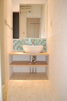 タモ材で造作した洗面台の上に置き型の洗面器。シンプルな空間に。