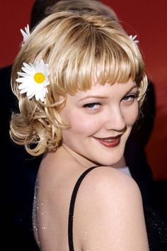 DREW BARRYMORE Barrymore transforms into a modern-day flower child at the 1998 Academy Awards, accessorizing her chin-length layered bob with a trio of daisies. #hair #hairstyle #celebrityhair