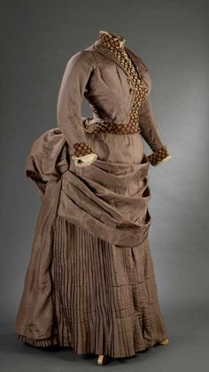 "Day dress ca. 1885. Chestnut silk gros de Tours. Bodice is a faux jacket with velvet print ""blouse"" and cuffs. Covered buttons. Pleated skirt with draped apron. Daguerre Auctions"