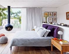 The master bedroom of a São Paulo home designed by the Campana brothers opens to a wraparound terrace. Carlos Regazzoni paintings hang behind the Maxalto bed, and the fireplace is by Focus | archdigest.com