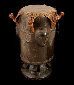 Tambour cylindrique -  Tambour vertical à une membrane et six chevilles. Caisse avec trois sculptures mascoïdes - Baoulé - Gouro - Côte d'Ivoire