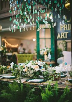 Green geode hanging installation for a wedding over a farm table with white and peach flowers and vintage green place settings