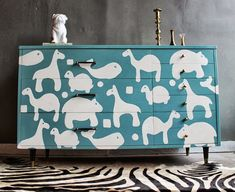 Why not? Up-cycle a dresser by applying hand drawn animal shapes that you can create with a French Curve set. Paint your dresser - this is the base coat color. Now cut out carefully with an x-acto knife. Assemble shapes on butcher paper to get your lay-out; peel and stick and use acrylic matter medium to seal the edges. Paint over the shapes, preferably with Glass enamel, and peel shapes off while paint is still tacky. This one is from etsy.