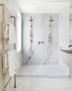 incredible marble double shower in this modern bathroom with brass fittings