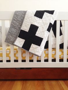 """this beautiful, modern quilt has black plus signs stretching across the quilt top and is quilted with diagonal lines stretching from edge to edge [quilted with black thread]. backed with black and white """"sketch"""" fabric and bound with black + white stripes to tie it all together. white + warm batting is sandwiched between high quality fabric. the finished quilt measures 36""""x44"""" and is hand bound for a perfectly clean edge. the size is great for snuggling your babe..."""