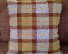 This luxury handmade cushion is made from the finest authentic Harris Tweed sourced from the Hebrides in Scotland. Harris Tweed Cushion :- Handmade Size – 20 x 20 inches. Colour – Light grey Filling – Microfiber. 3 functioning self covered buttons. Authentic Harris Tweed orb label.  Due to delicate nature of the embroidery and material, I recommend dry clean only.  Love Jacqueline, Talla Tweed Designs