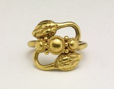 Romano-British, 1st-2nd century AD. Gold snake finger-ring, double-headed (Type Bii). The ring has a simple circular-sectioned hoop, terminating in turned-back snake-heads of the standard stylised form. The crossing area of the hoop at the front is covered with a row of three gold bosses surrounded by beaded wire, with small gold globules at the sides.
