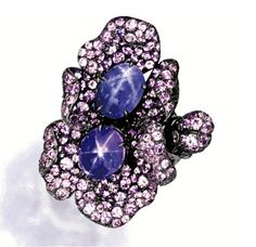 PURPLE STAR SAPPHIRE AND COLOURED SAPPHIRE RING Of floral design, centring on two star sapphires of purple and violet hues weighing 8.34 and 5.92 carats respectively, to petals set with circular-cut coloured sapphires of matching hues together weighing approximately 4.50 carats, mounted in 18 karat blackened gold.