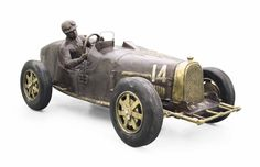 A lifesize French burnished and patinated bronze sculpture of racing driver maurice trintgnant at the wheel of his type 51 Bugatti racing car