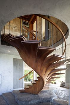 A long set of African mahogany and teak stairs designed by a woodworking craftsman to look like a curved philodendron plant.