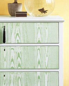 An embossed-paint rocker and a combing tool, dragged through a green glaze, leave a faux-bois (wood-grain) imprint. #dresser #decor #DIY